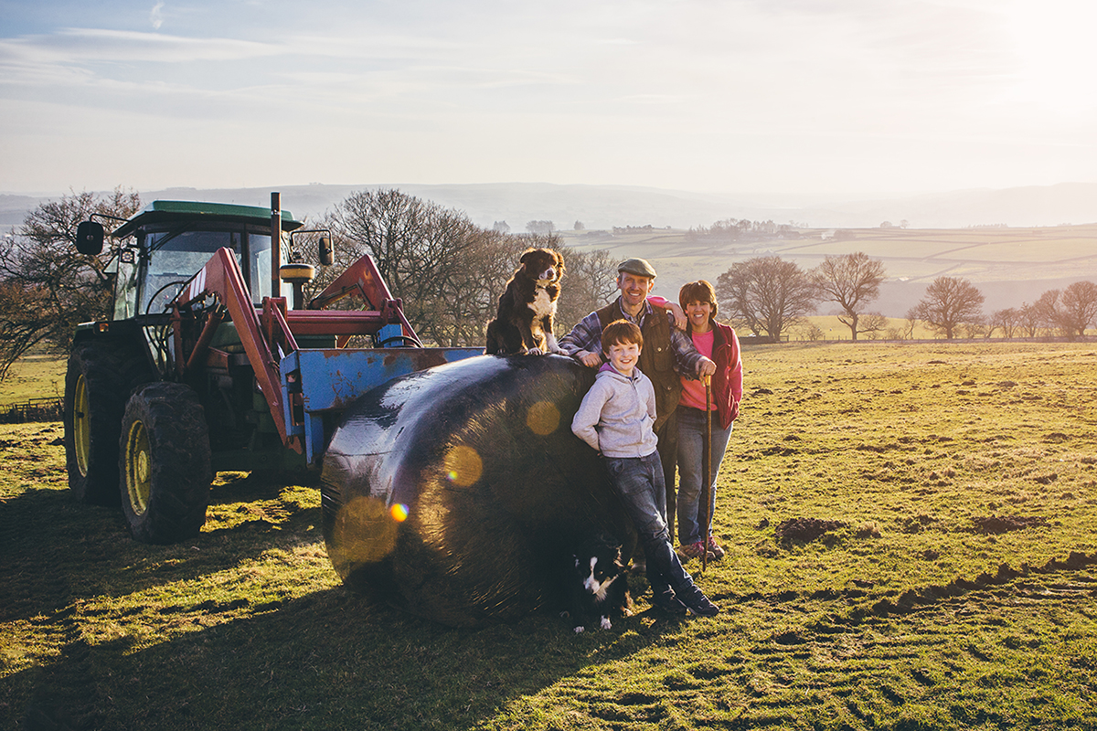 Environmental portrait of a two generation family of farmers with their tractor